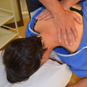 chiropractor's hands on patient's back
